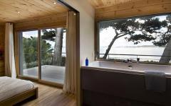 Intérieur chambre maison en bois avec vue sur la mer