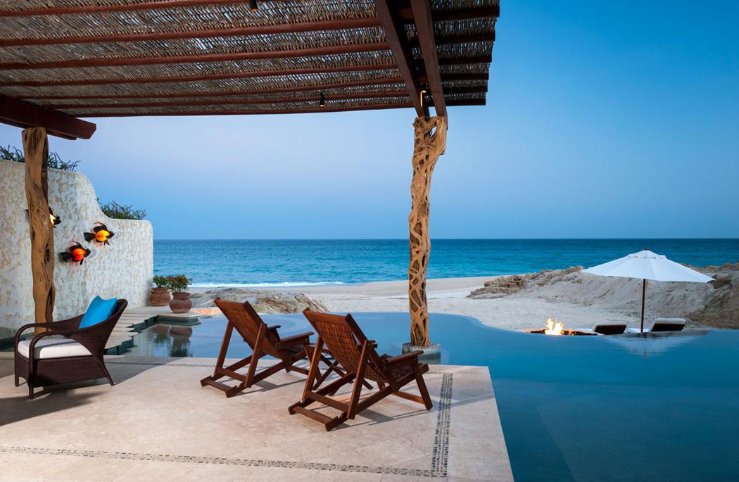 Une terrasse ombragée donnant sur une piscine à débordement face à locéan villa de luxe avec vue sur la plage